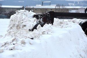 Nakladač odhŕňa snehové záveje na ceste pred obcou Novosad