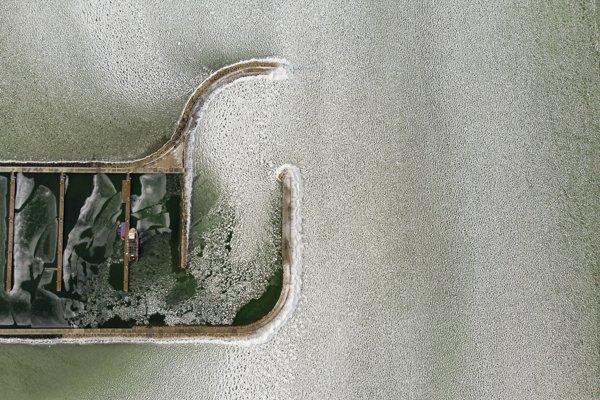 Pohľad na mólo s jachtami na zamrznutom jazere Balaton v maďarskej obci Balatonfenyves