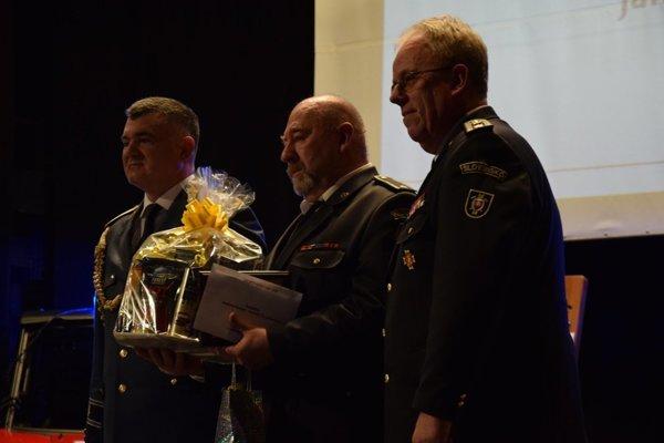 Ján Švajčiak (uprostred) pri preberaní ocenenia.