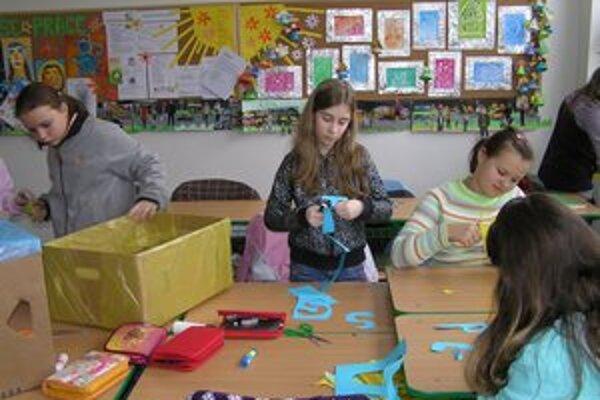 Žiaci pripravujú škatule na zber triedeného odpadu v škole.
