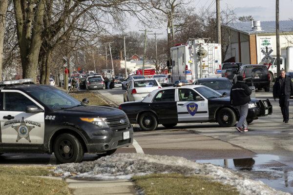 Policajti a hasiči zasahujú v budove, ktorá patrí miestnemu výrobnému podniku.
