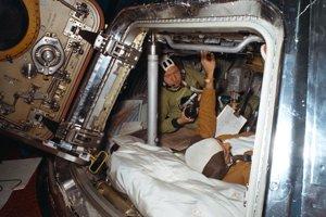 Astronaut Alan L. Bean (v popredí( a kozmonaut Alexej Archipovič Leonov počas prípravy na experiment Apollo-Sojuz v roku 1975.  Nachádzajú sa v trénovacom moduli Apollo. Tréning im simuloval prvý deň na obežnej dráhe Zeme.
