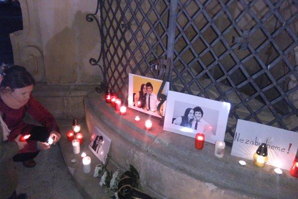 Účastníci zhromaždenia zapálili sviečky pri portrétoch zavraždených.