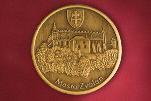 Minca Zvolena s reliéfom zámku.