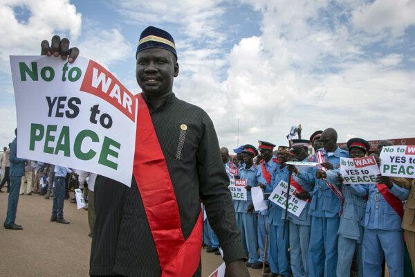 """Muž drží transparent s nápisom """"Nie vojne, áno mieru"""" počas návratu prezidenta Južného Sudánu Salvu Kiira na letisku v Džube v piatok 22. júna 2018."""