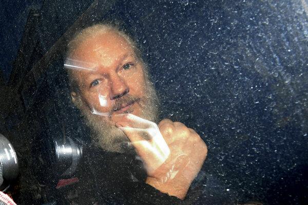 Julian Assange pri prevoze z ambasády.