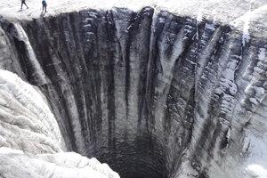 Veľký zvislý otvor v ľadovci Plaine Morte. Cez podobné otvory uniká voda k ložisku ľadovca pri každoročnom odtoku z preplneného jazera na ľadovci.
