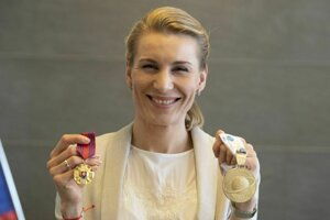 Olympijská víťazka, majsterka sveta a členka Vojenského športového centra (VŠC) Dukla Banská Bystrica Anastasia Kuzminová pózuje so zlatou pamätnou medailou prvého stupňa ministra obrany (vľavo) a zlatou medailou z MS (vpravo).