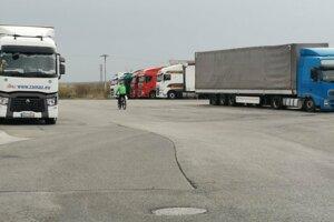 Jazda medzi kamiónmi. Úsekom prechádzajú aj chodci.