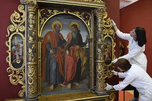 Reštaurátorka Mária Levendovská (dole) a Lidia Macurak (hore) pri skladaní častí Oltára sv. Petra a Pavla.