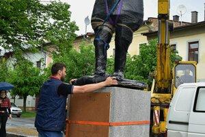 Muž usmerňuje hliníkovú sochu Milana Rastislava Štefánika počas pripevnenia na podstavec.