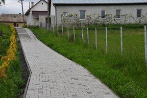 Časť vynoveného chodníka v obci Holiša.