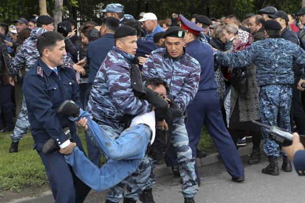 Kazašskí policajti zatýkajú demonštranta počas protestuv meste Nursultan.
