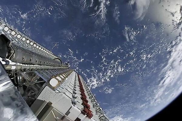 """Záber z vysielania štartu misie Starlink. Vľavo vidno """"zásobník"""" so 60 satelitmi Starlink."""