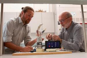 Doktorand Jacob George a profesor Greg Clark pozorujú protézu LUKE arm, ktorú využívajú pri experimentoch.