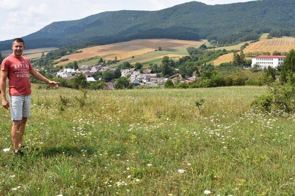 Starosta Domaniže František Matušík ukazuje, kde sa objavuje medvedica. V pozadí kopec a pod ním pokosené polia s obilím. Medvedica prichádza z tejto strany a až do blízkosti obydlí.
