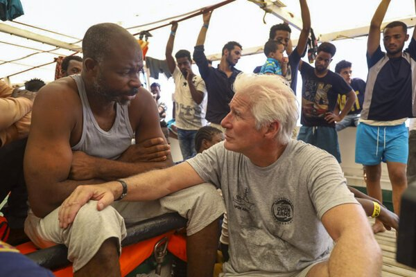 Richard Gere na palube lode hovorí s utečencami.