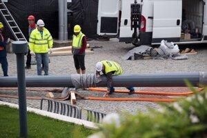 Práce na vztýčení stožiara pred budovou parlamentu.