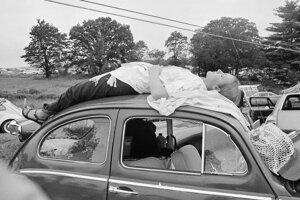 Mladá žena leží na streche svojho auta počas prvého ročníka legendárneho hudobného festivalu Woodstock.
