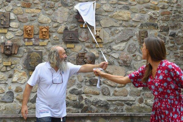 Riaditeľ festivalu Roman Vykysalý a herečka Lucia Rózsa Hurajová odhaľujú umelecký reliéf s podobizňou Magdy Pavelekovej.