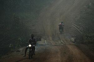 Obyvatelia idú na motocykloch cez dym z lesných požiarov v časti brazílskej Amazónie v štáte Rondonia, časť brazílskej Amazonky.