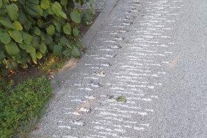 Odtlačky v asfalte po vojenskej technike.