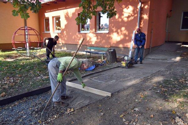 Na snímke pracovníci sociálneho podniku opravujú chodník v miestnej materskej škole vo Veľatoch.