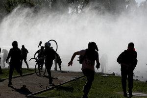 Demonštranti utekajú pred slzným plynom. Santiago, 20. október 2019.
