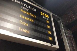 Tabuľa na stanici oznamuje meškania niektorých vlakov po tom, čo sa vykoľajil vozeň nákladného vlaku.