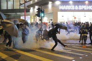 Demonštrant odkopáva slzotvorný granát počas potýčok s políciou pred nákupným centrom v Hongkongu v nedeľu 10. novembra 2019.