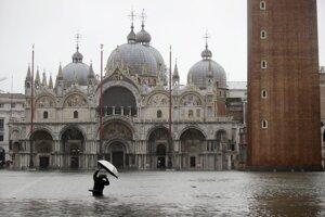 Turista na zaplavenom Námestí svätého Marka v Benátkach.