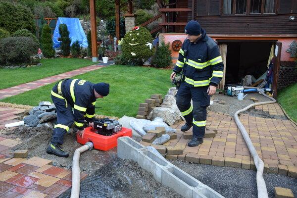 Dobrovoľní hasiči z Bodíc, Liptovského Trnovva aj Liptovskej Ondrašovej pomáhajú odčerpávať vodu.