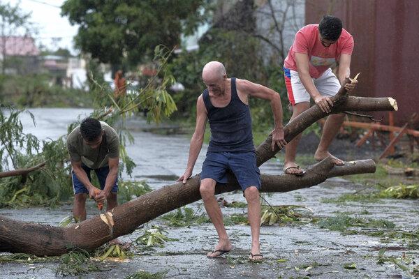Muži pília strom, ktorý vyvrátil tajfún Kammuri vo filipínskom meste Legazpi 3. decembra 2019.