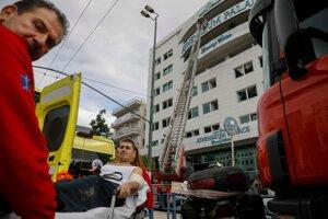 Záchranka odváža muža pár minút po vypuknutí požiaru v hoteli Athenaeum Palace hotel.