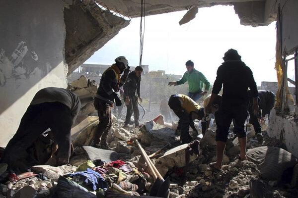 Biele helmy pátrajú v troskách po nálete v provincii Idlib.
