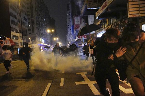 Hongkonskí demonštranti utekajú po tom, ako polícia použila slzotvorný plyn.