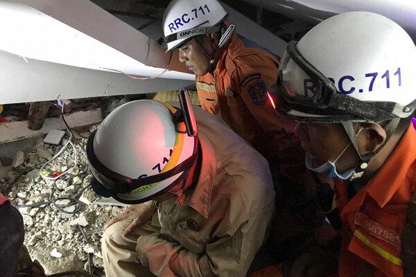 Záchranári prehľadávajú trosku zrútenej budovy v Kambodži.