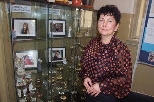 Riaditeľka školy pri vitrínke s fotkami obetí nehody.