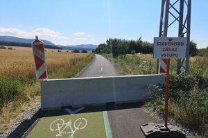 Cykloželeznička a čerstvopoložené betónové zátarasy v júli 2019.