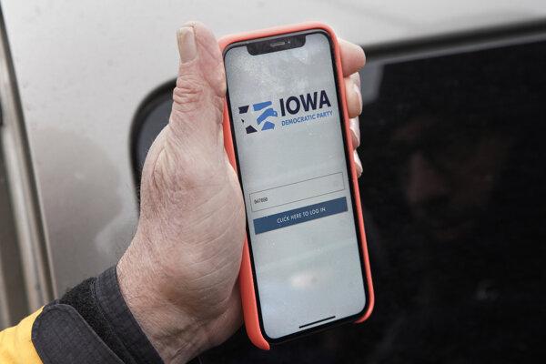 Volebný komisár Carl Voss drží iPhone, v ktorom ukazuje výsledky volebných zhromaždení tzv. caucusy Demokratickej strany v Iowe na app-ke v meste Des Moines 4. februára 2020.