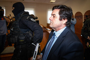 Kukláči privádzajú obžalovaného Mariana Kočnera do pojednávacej miestnosti.