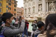 Čínsky turista s ochranným rúškom na tvári si fotí fontánu Trevi v Ríme.