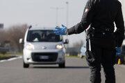 Taliansky policajt zastavuje auto pred uzavretou zónou.
