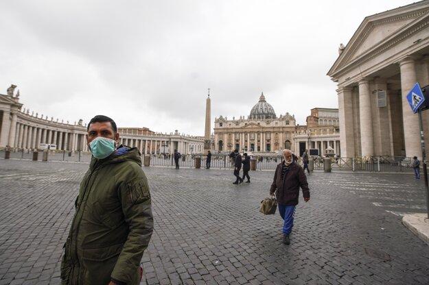 Muž s ochranným rúškom na tvári kráča po prázdnom Námestí sv. Petra vo Vatikáne.