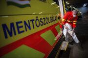 Pracovník maďarskej záchrannej služby sa oblieka do ochranného obleku.