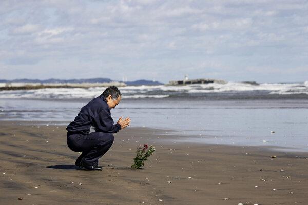 Muž pri pietnej spomienke na pobreží vo Fukušime.