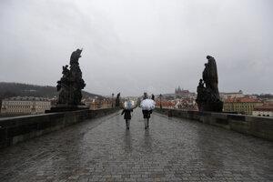 Ľudia kráčajú po prázdnom Karlovom moste v Prahe.
