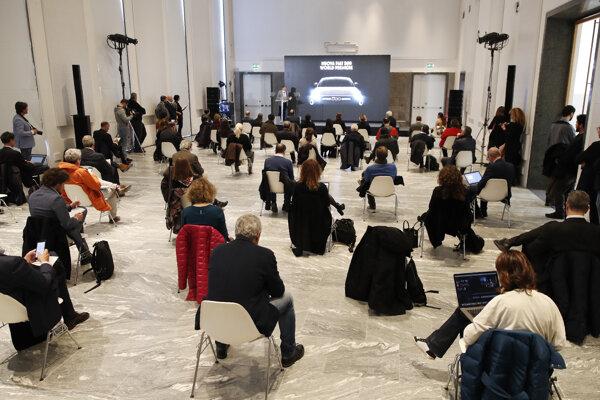 Ľudia sedia v odporúčanej vzdialenosti počas predstavenia nového elektromobilu Fiat 500e v Miláne, v Taliansku.