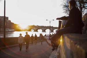 Ľudia kráčajú vedľa brehu rieky Seiny počas západu slnka 15. marca 2020 v Paríži.