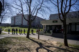 Ľudia stoja v rade pred poštou s dostatočným odstupom v maďarskom meste Pécs.